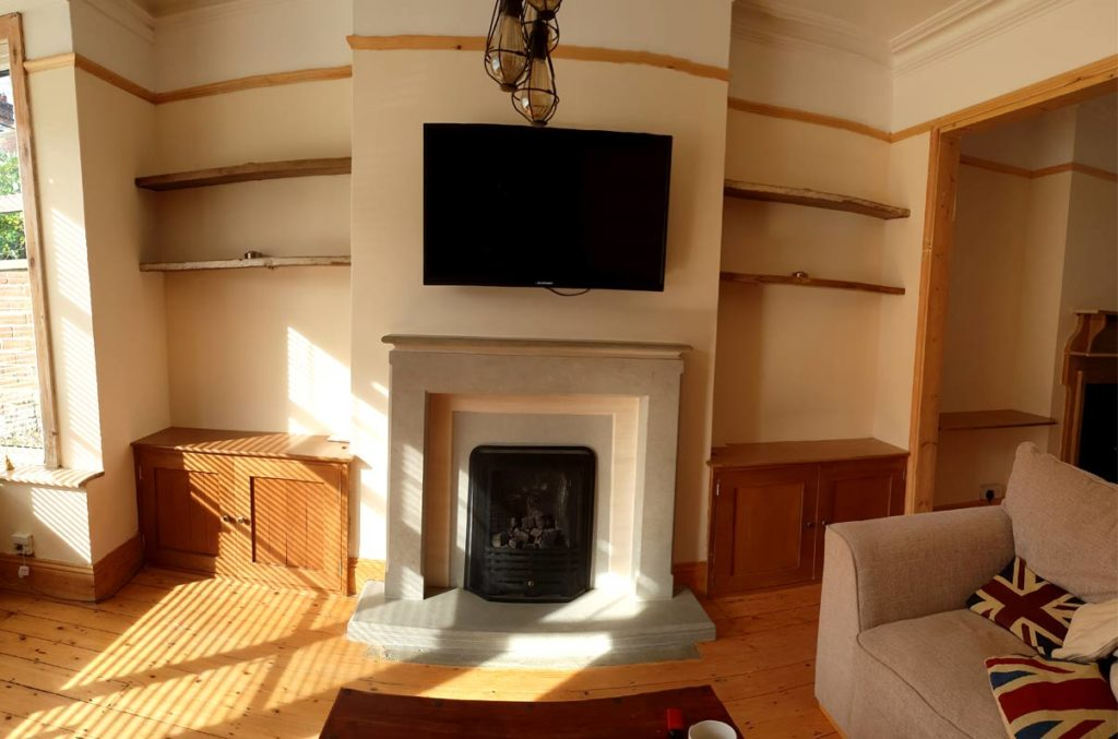 This picture shows the chimney breast and alcoves with custom built cupboards and shelving created by Made to Alder.